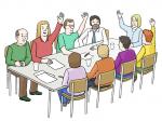 Ein eckiger Tisch mit Menschen, die abstimmen